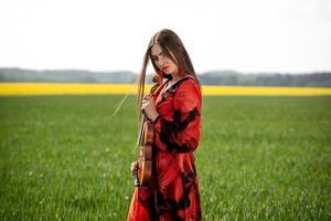 Jeune femme en robe rouge avec violon dans un pré vert - image photo