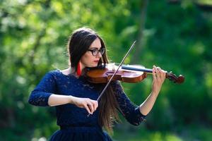 jeune femme jouant du violon au parc. faible profondeur de champ - image photo