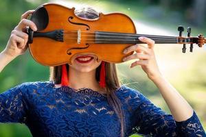 portrait d'une jeune femme positive. une partie du visage est recouverte par le manche du violon - image photo