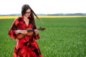 Jeune femme en robe rouge jouant du violon dans un pré vert - image photo