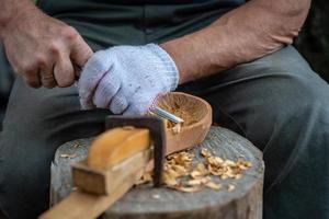 artisan démontre le processus de fabrication de cuillères en bois photo
