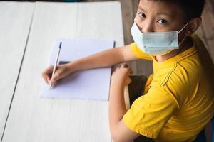 concept d'éducation, d'école et de pandémie - garçon étudiant portant un masque médical de protection du visage pour se protéger des maladies virales photo