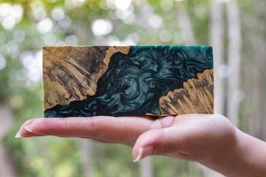 main tenant la résine époxy stabilisant afzelia burl bois exotique fond de lave rouge photo