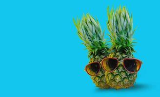 ananas portant des lunettes de soleil rouges sur fond bleu isolé photo