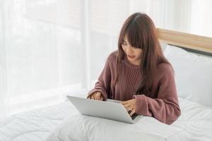 femme asiatique travaillant avec un ordinateur portable sur le lit à la maison photo