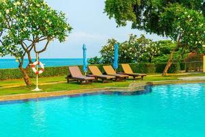chaise piscines ou lits et parasols autour de la piscine avec fond de mer - concept de vacances et de vacances photo