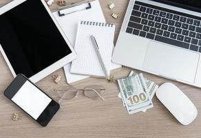 ordinateur portable avec des fournitures de bureau et de l'argent sur la table. photo