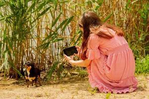 Teen girl taking photo son chien avec l'appareil photo du téléphone mobile