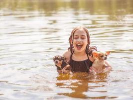 l'enfant aime les relations avec les chiens. une fille avec deux chihuahuas nage dans la rivière. photo