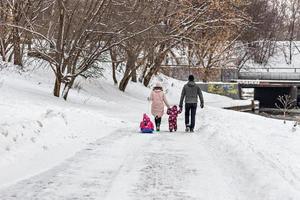 une famille avec deux enfants dans un traîneau lors d'une promenade dans le parc photo