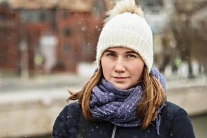 portrait d'une jeune belle fille souriante heureuse sur le fond de la ville. mode d'hiver, concept de vacances de Noël. photo