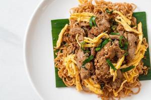 nouilles instantanées sautées au porc et aux œufs - style de cuisine de rue locale asiatique photo