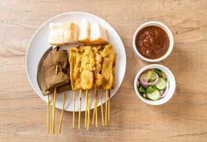 satay de porc et satay de foie avec du pain et de la sauce aux arachides et des cornichons qui sont des tranches de concombre et des oignons au vinaigre - style de cuisine asiatique photo