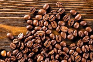 Macro image de grains de café torréfiés sur fond de planche de bois texturé marron. photo