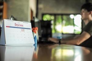 calendrier en gros plan sur la table avec un ouvrier flou tapant le clavier de l'ordinateur en arrière-plan. concept de travail à domicile. mot thaï sur le calendrier signifie juin en anglais photo