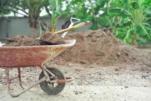 Chariot en acier gros plan transportant le sol avec des pelles avec un tas de sol flou et un paysage en arrière-plan photo