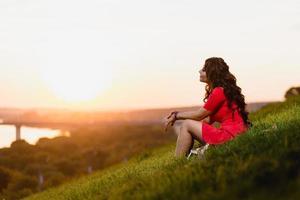 belle jeune fille assise sur une pente couverte d'herbe verte photo