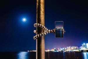 à l'aide d'un smartphone sur un trépied pliable avec une longue exposition de la mer la nuit photo