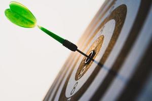 flèches de fléchettes vertes au centre de la cible sur fond de ciel. objectif commercial ou objectif de réussite et concept de gagnant. photo