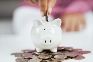 gros plan de la main d'une femme d'affaires mettant de l'argent dans une tirelire pour économiser de l'argent. économiser de l'argent et concept financier photo