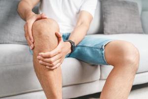 l'homme souffrant de douleurs au genou assis sur le canapé tient et masse son genou douloureux. photo