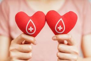mains de femme tenant un coeur rouge avec signe de donneur de sang. concept de soins de santé, de médecine et de don de sang photo