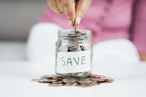 les femmes mettent de l'argent à la main dans un bocal en verre pour économiser de l'argent. économiser de l'argent et concept financier photo