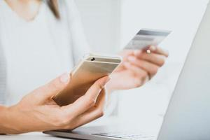 main de femme tenant une carte de crédit et un téléphone intelligent à l'aide d'un ordinateur portable. paiement en ligne, concept d'achat en ligne photo