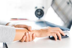 femme en gros plan tenant sa douleur au poignet en utilisant un ordinateur pendant longtemps. concept de syndrome de bureau. photo