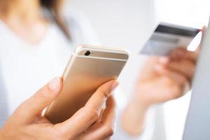 femme utilisant un téléphone intelligent avec une carte de crédit. achats en ligne, finances, publicité en ligne. photo