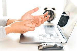 gros plan femme tenant sa douleur à la main de l'utilisation de l'ordinateur depuis longtemps. concept de syndrome de bureau. photo