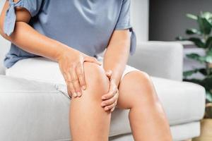 gros plan sur une femme potelée assise sur le canapé et ressentant une douleur au genou et elle se masse le genou. concept de soins de santé et médical. photo