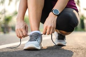 gros plan du coureur de la jeune femme attachant ses lacets. concept de santé et de remise en forme. photo