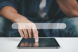 gros plan d'un jeune homme utilisant une tablette sur le canapé. recherche, navigation, achats en ligne, réseau social. photo