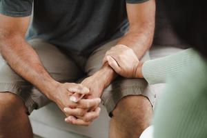 amie ou famille assise et se tenant la main pendant qu'elle encourage l'homme dépressif mental, un psychologue fournit une aide mentale au patient. concept de santé mentale ptsd photo