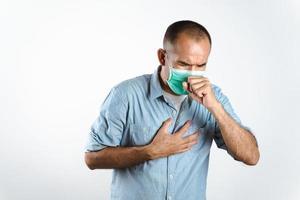 homme portant un masque facial éternuant ou toussant sur sa main pour empêcher la propagation du virus covid-19 ou du virus corona sur fond blanc. photo