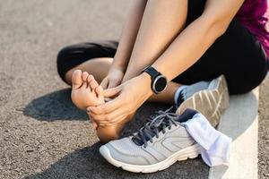 accident de jambe de blessure en cours d'exécution- coureur de femme de sport blessant tenant la cheville entorse douloureuse dans la douleur. athlète féminine souffrant de douleurs articulaires ou musculaires et de problèmes de sensation de douleur dans le bas du corps. photo