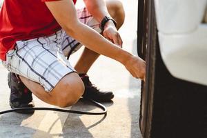 gros plan d'un homme asiatique gonflant un pneu dans la station-service. photo