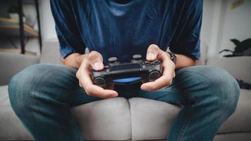 Jeune bel homme excité tenant un contrôleur de manette de jeu jouant à un jeu vidéo assis sur le canapé à la maison photo