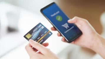 jeune femme tenant une carte de crédit et utilisant un téléphone intelligent pour les achats en ligne, les services bancaires sur Internet, le commerce électronique, dépenser de l'argent, travailler à domicile photo