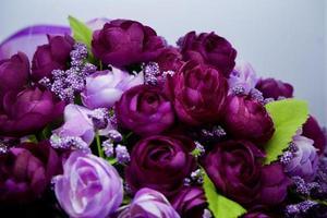 fleurs artificielles violettes et roses, feuilles vertes sur fond blanc. fleur de printemps, pâques, journée de la femme, fête des mères, concept du 8 mars. espace de copie. photo