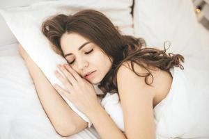 Jeune femme dormant paisiblement dans la chambre avec des draps frais blancs photo