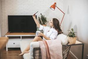 jeune femme fait selfie assis sur un canapé à la maison. photo