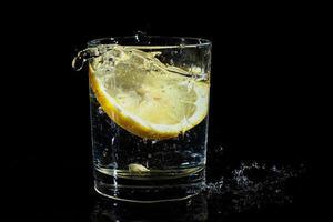 eau avec du citron dans un verre sur fond noir. photo