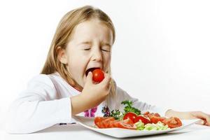 jolie petite fille avec une assiette de légumes frais photo