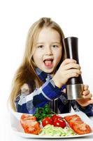jolie petite fille avec une boîte à salade et à poivre photo