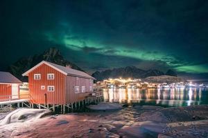 Maison en bois rouge dans un village de pêcheurs avec des aurores boréales sur la ville de reine en hiver la nuit photo