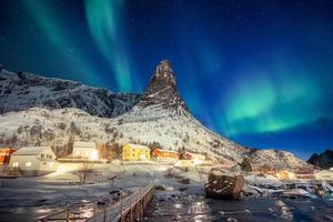 village scandinave coloré avec des aurores boréales au-dessus de la montagne de pointe aux lofoten photo