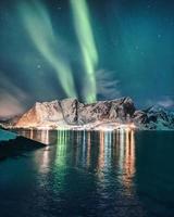 aurores boréales, aurores boréales sur la montagne enneigée avec village lumineux à hamnoy aux îles Lofoten photo