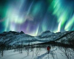 Homme voyageur alpinisme sur une colline enneigée avec des aurores boréales dans le ciel nocturne à l'île de Senja photo